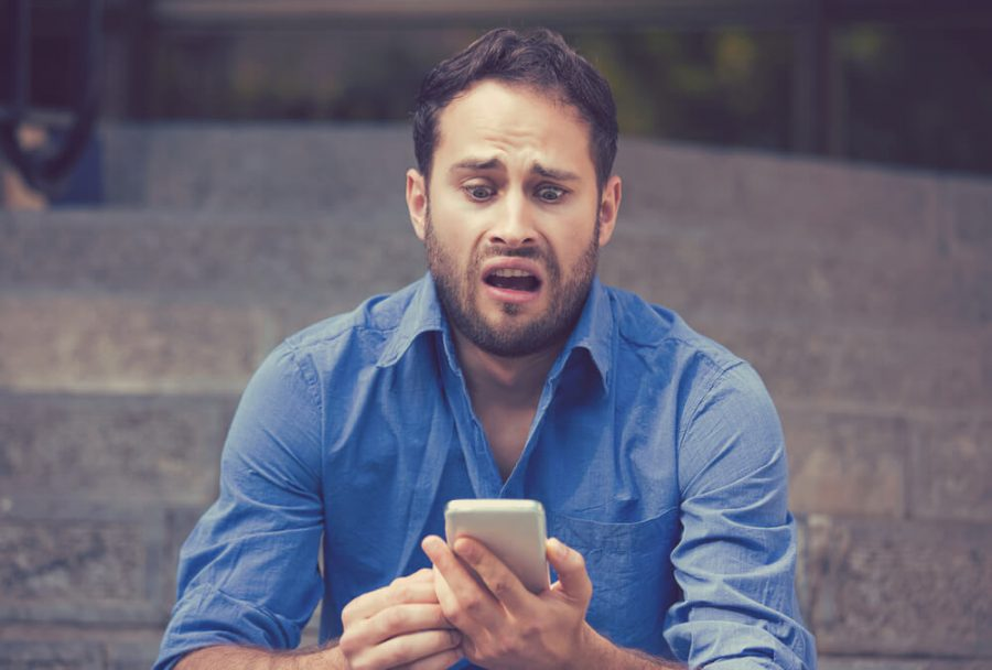 Anxious upset scared man looking at phone