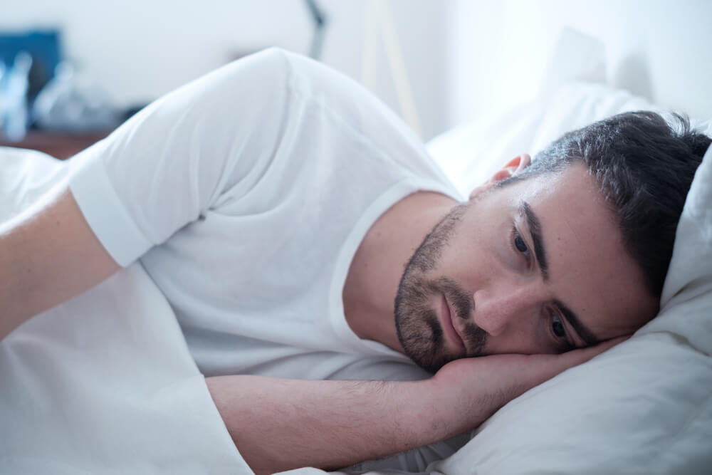 Depressed man lying in his bed