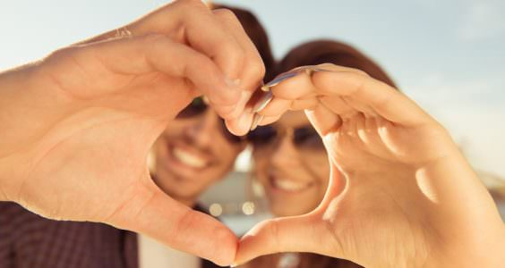 Happy romantic couple in love gesturing a heart