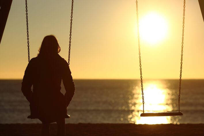 woman sitting on the swing at sunset