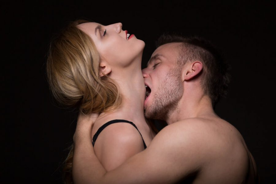 Man passionately kissing and biting a woman in the neck