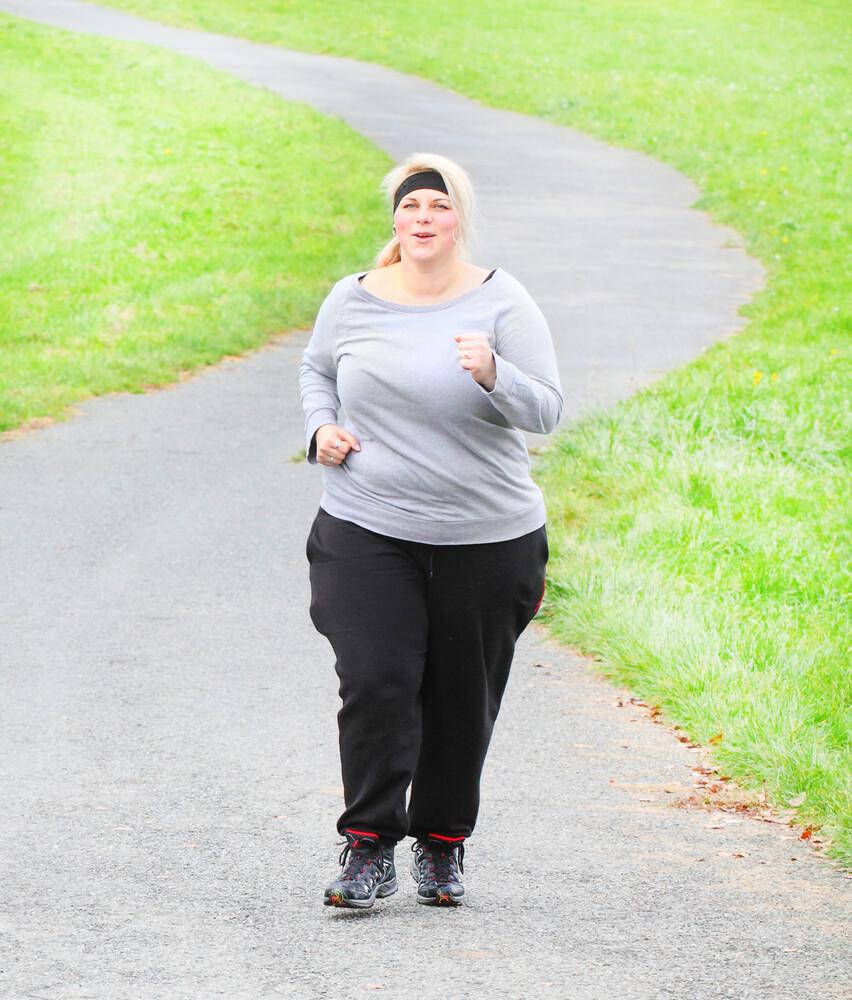 Overweight woman running. Weight loss concept.