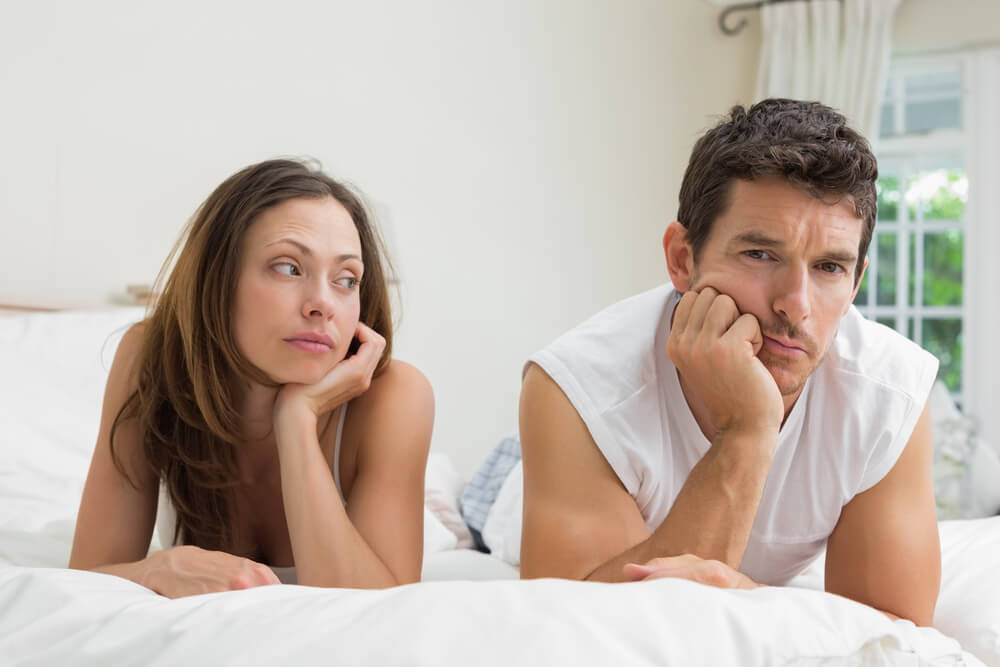 Unhappy couple not talking after an argument in bed