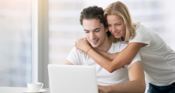 Young happy people looking at laptop