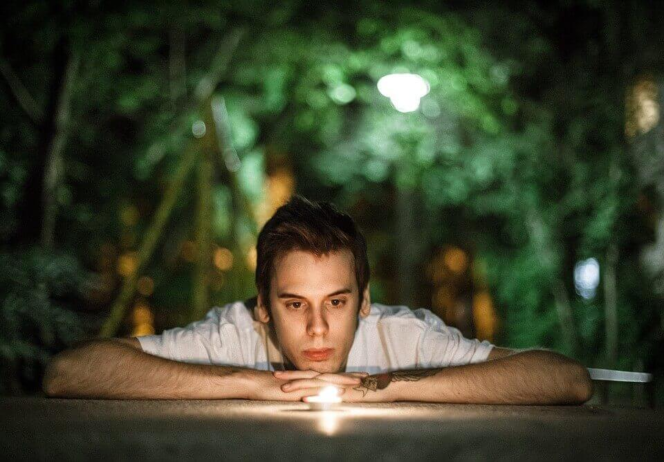 Young man staring at a candle
