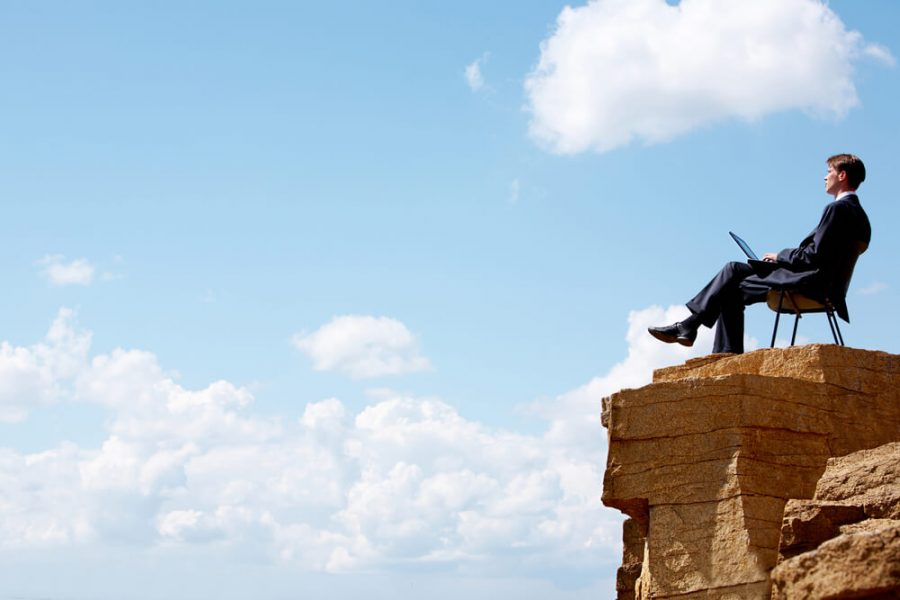 businessman sitting on the chair on edge of cliff