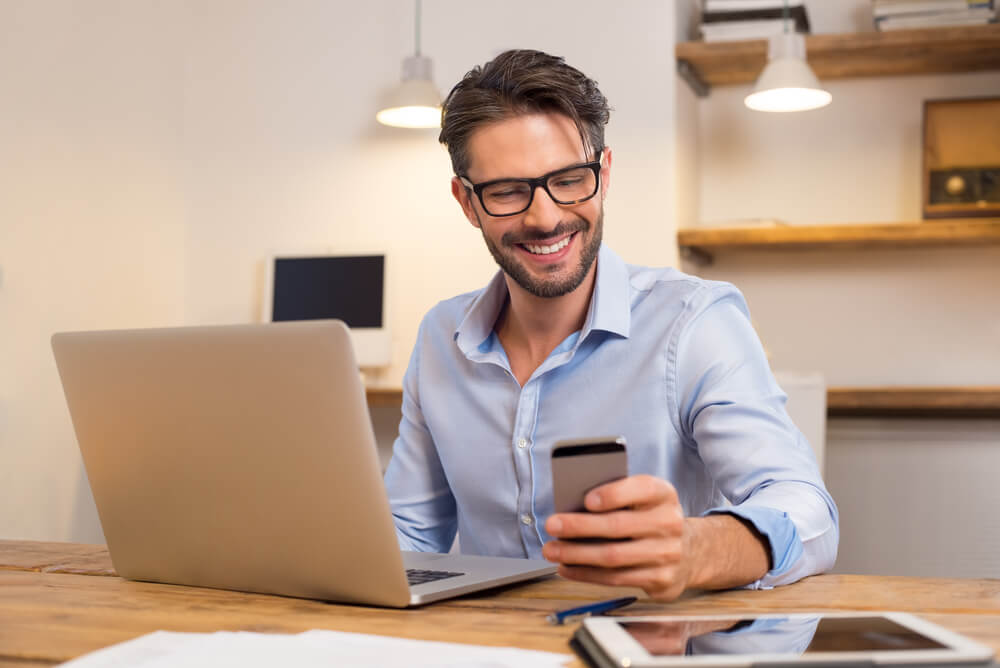 man smiling while reading a text