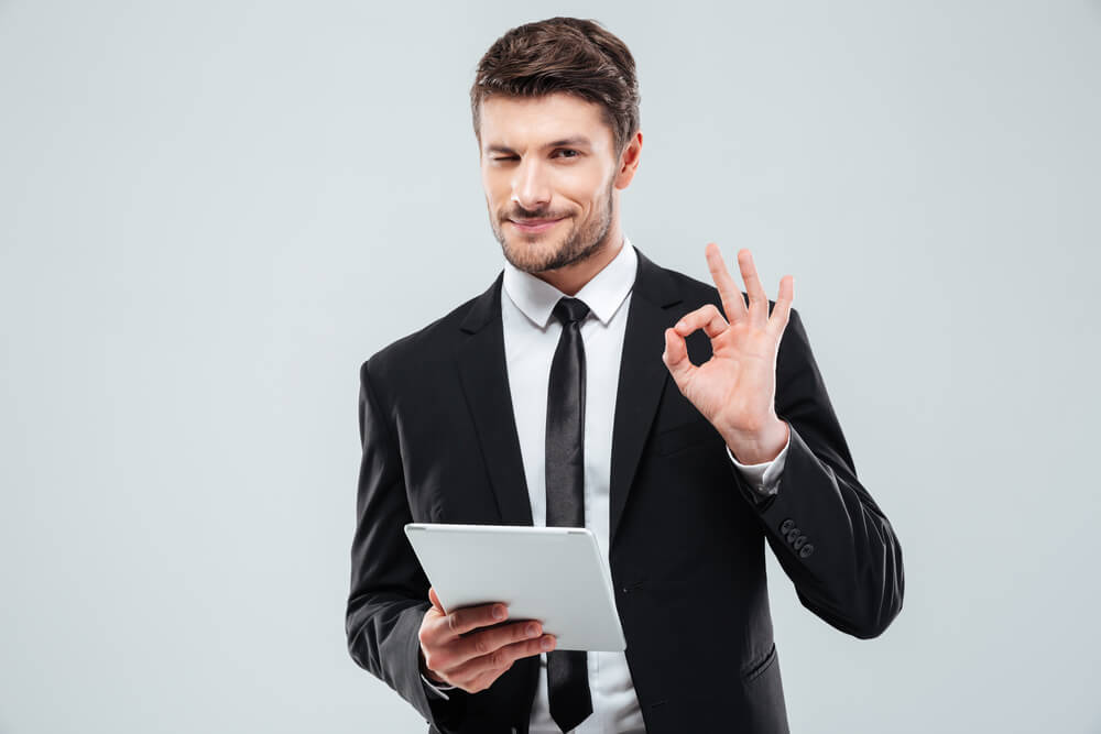 man with tablet winking and showing ok sign