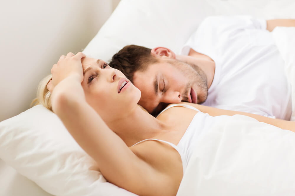 unhappy woman with sleeping man in bed