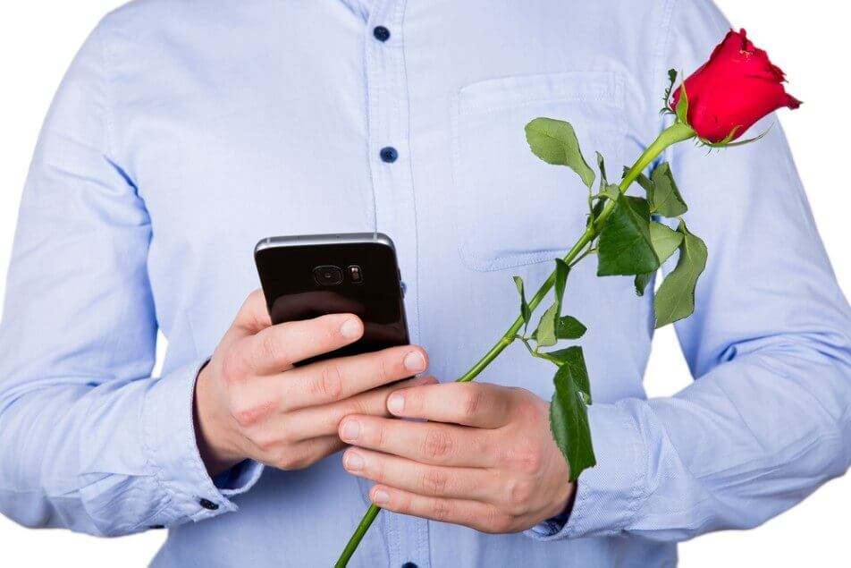 young guy holding a red rose and texting